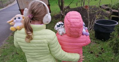Man sieht ein kleineres Mädchen in einer orangen Jacke mit zwei Kuscheltieren auf der Schulter und links daneben ein etwas grössere Mädchen mit gelber Jacke und Ohrenschützern mit einem Kuscheltier auf ihren Schultern. Sie stehen vor dem Garten draussen.