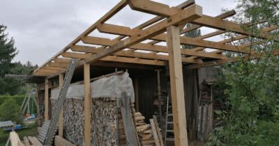Man sieht den Dachbau für einen Unterstand. Unten ist viel Holz zu sehen.