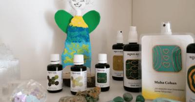 Man sieht einen Ausschnitt vom Gestell in der Praxis von Jeannine. Es sind Engelessenzen von Ingrid Auer, Edelsteine und ein grüner selbstgebastelter Engel zu sehen.