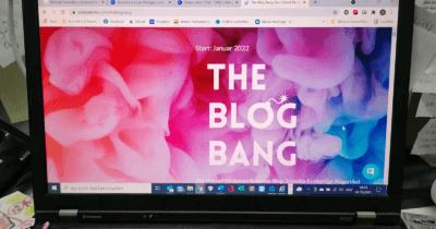 Man sieht einen aufgeklappten Laptop auf dem die Startseite mit dem Schriftzug The Blog Bang zu sehen ist. Die Farben sind rot, pink, blau und die Schrift ist weiss.