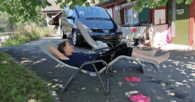 Man sieht Jeannine schlafend in einem Liegestuhl unter einem Baum. Daneben liegen rote Clocks und dahinter ist ein Auto und der Eingang eines Hauses zu sehen.
